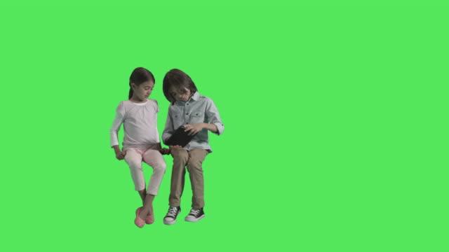two arab children sitting reading on digital tablet - sitting stock videos & royalty-free footage