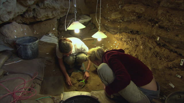 zi two archaeologists digging in blombos cave excavation site and discovering a specimen / south africa - archaeologist stock videos & royalty-free footage
