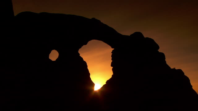 Two arches silhouetted in front of nice sunset with wispy clouds and deep colors