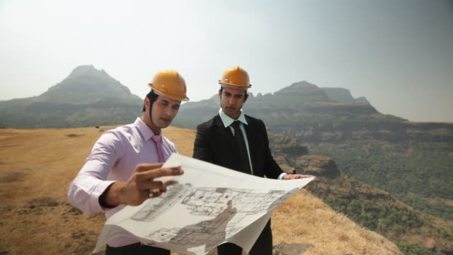 Two architect planning a construction on the cliff of mountain