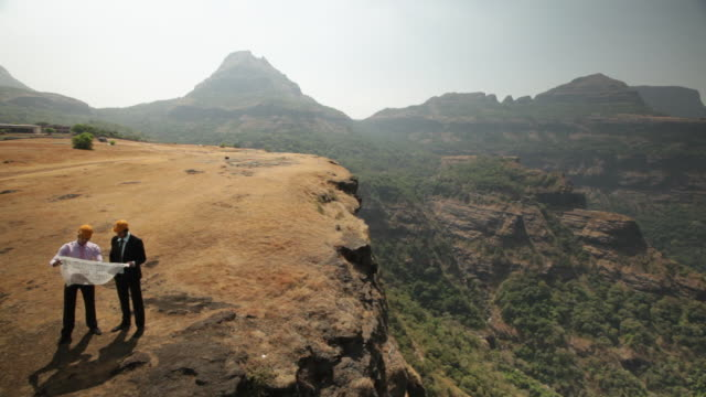 vídeos de stock, filmes e b-roll de two architect planning a construction on the cliff of mountain  - camisa e gravata