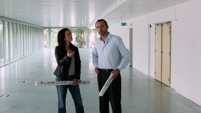 WS Two architects holding plans in an empty office / Brussels , Brabant, Belgium