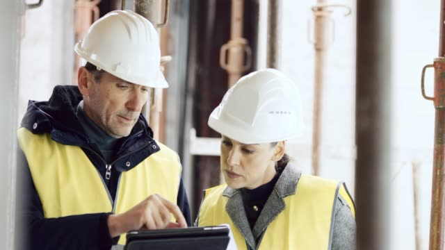 two architects standing at the construction site and talking about details of the plan on the digital tablet - scaffolding stock videos & royalty-free footage