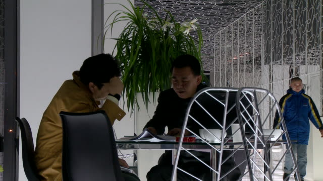 ms two architects talking over plans at coffee table, beijing, china - coffee table stock videos & royalty-free footage