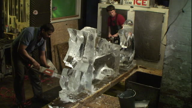 Two artists use chainsaws to carve ice sculptures.