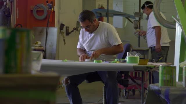 ws zi ms two artists working in workshop, malibu, california, usa - dreiviertelansicht stock-videos und b-roll-filmmaterial