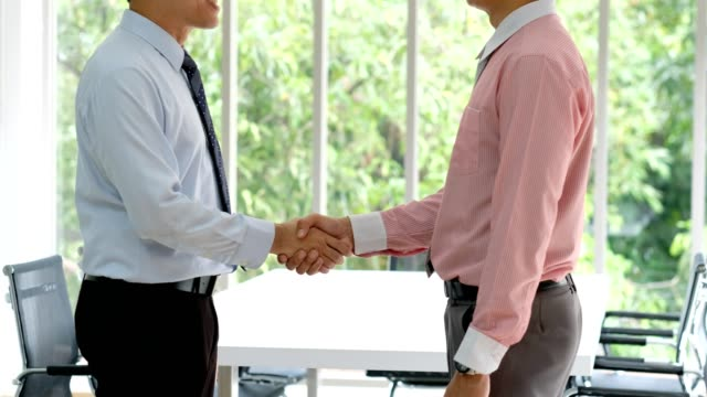 two asia businessmen partners handshake at office background, business concept, profitable agreement, co-operation - ambassador stock videos & royalty-free footage