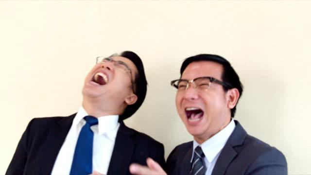 Twee Aziatische zakenmannen staan lachen waanzinnig. En een vinger wijzend naar de camera