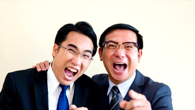 two asian business men are standing laughing madly. and a finger pointing to camera - ridere video stock e b–roll