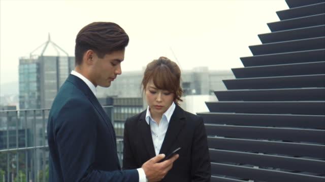 2 つのアジアのビジネスパートナーの散歩、屋上 - 土曜日点の映像素材/bロール