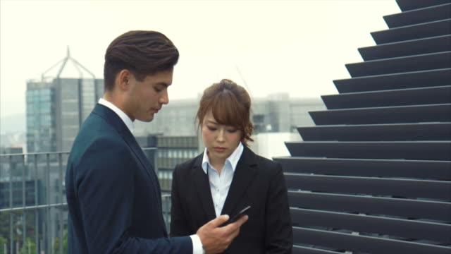 屋上 (スローモーション) を歩いて 2 アジア ビジネス パートナー - 土曜日点の映像素材/bロール