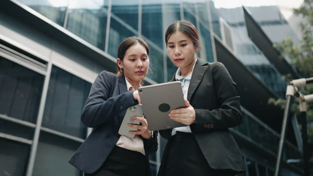 two asian business people talking about business on digital tablet - using digital tablet stock videos & royalty-free footage