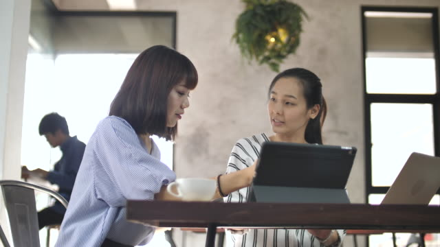 Two Asian Business people working in cafe together, Slow motion