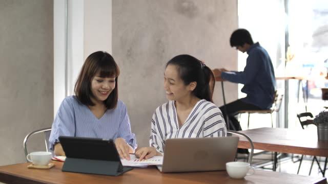 2 アジアのビジネス人、一緒にカフェで働いてスローモーションします。 - 談笑する点の映像素材/bロール
