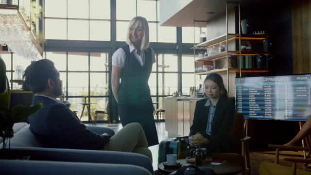 vídeos de stock, filmes e b-roll de dois viajantes de negócios asiáticos desfrutando do serviço do salão de primeira classe no aeroporto - área de embarque de aeroporto