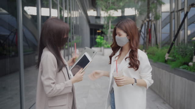 two asian business women wear surgical mask holding laptop going to office - two people stock videos & royalty-free footage