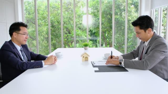 Zwei asiatische Geschäftsmann Zeichen Vertrag über Immobilien und Handschlag gegenseitig mit deal.partnership Geschäftskonzept.