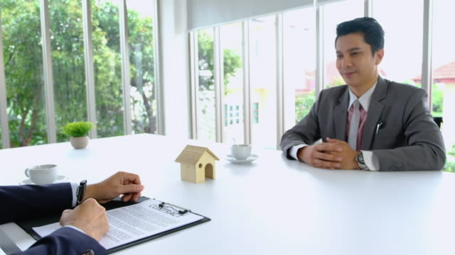 Two asian Businessman sign contract about real estate and handshake each other with business deal.partnership concept.