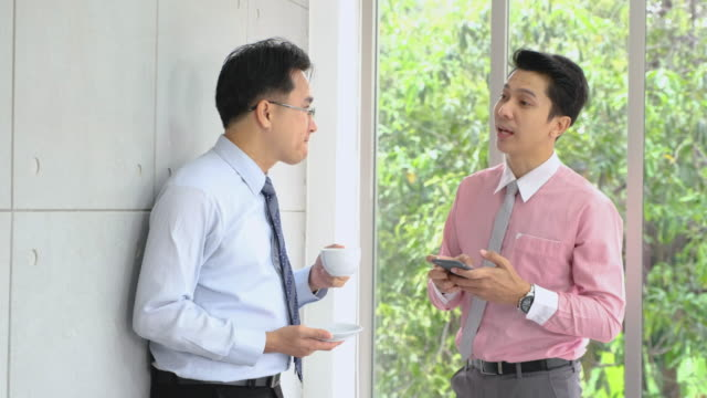 Two asian businessman talking in coffee break time in office cafeteria.