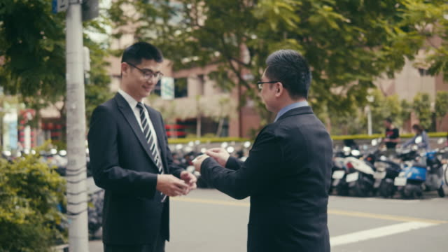 two asian businessmen exchanging business cards in the street - east asian ethnicity stock videos & royalty-free footage