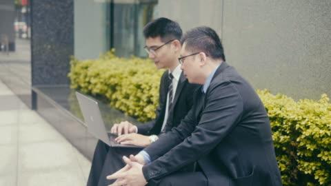 zwei asiatische geschäftsleute mit laptop auf der straße - chinese culture stock-videos und b-roll-filmmaterial