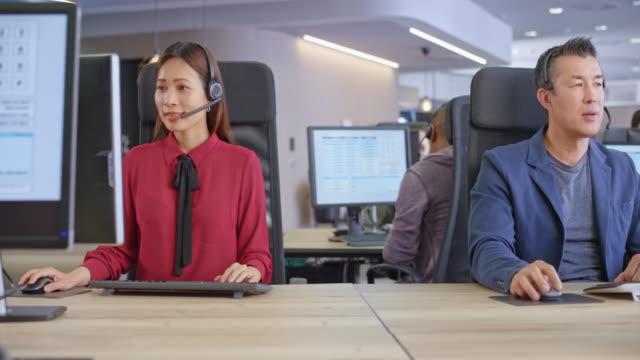 ds 2つのアジアのコールセンターエージェントは、彼らのステーションで働いています - コールセンター点の映像素材/bロール