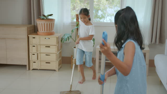 two asian child girl siblings cleaning and mopping the floor with a microfiber wet mop pad in the living room together with fun. - wet wet wet stock videos & royalty-free footage