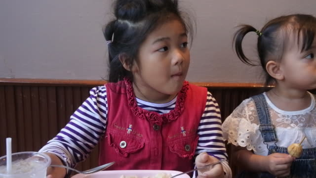two asian children eat in a restaurant. - vegetarian food stock videos and b-roll footage