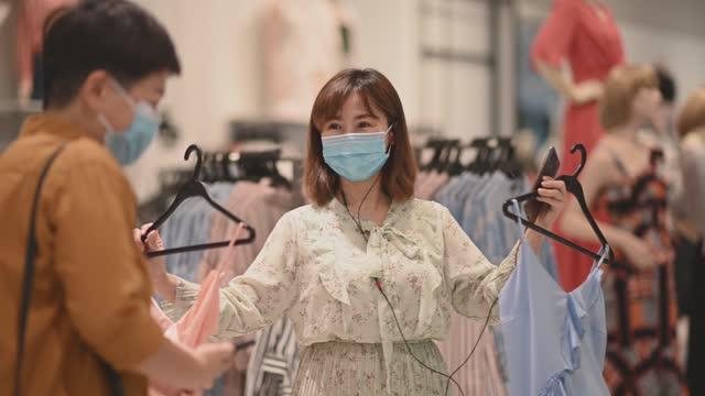 衣料品店でフェイスマスク付き服を選ぶ2人のアジアの中国人女性 - 店頭点の映像素材/bロール