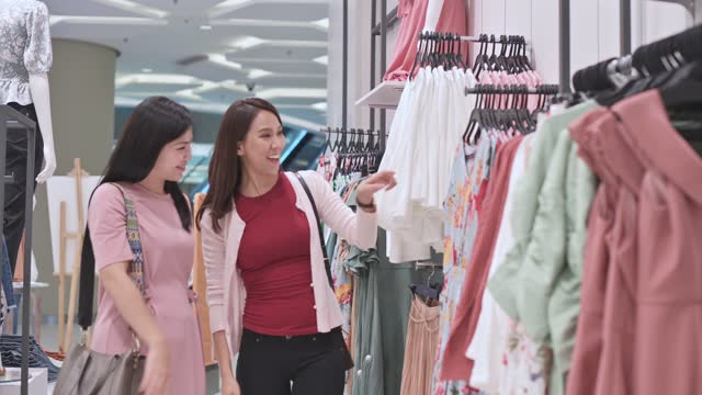 two asian chinese female choosing clothes with facemask at clothing store - clothes shop stock videos & royalty-free footage