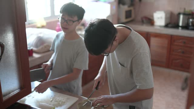 two asian chinese teenagers preparing food for reunion chinese new year - skill stock videos & royalty-free footage