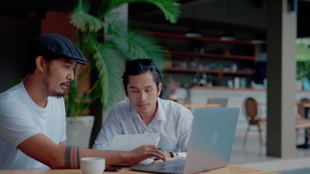 vídeos y material grabado en eventos de stock de dos compañeros de trabajo asiáticos sentados en la mesa y trabajando con computadora portátil en la cafetería al aire libre. - cultura de café