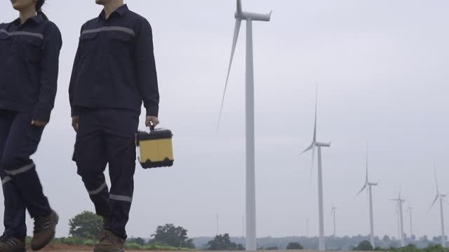 タイの風力発電所で安全な風力タービンの準備と進捗チェックを準備し、進捗状況チェックを行う統一検査エンジニアの2人のアジア人エンジニア。 - 送電線点の映像素材/bロール
