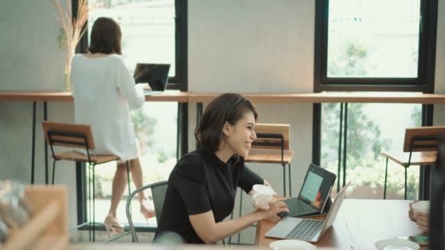 アジアの女性フリーランサー2人がノートパソコンを使ってコーヒーショップで働いている - コーヒーショップ点の映像素材/bロール