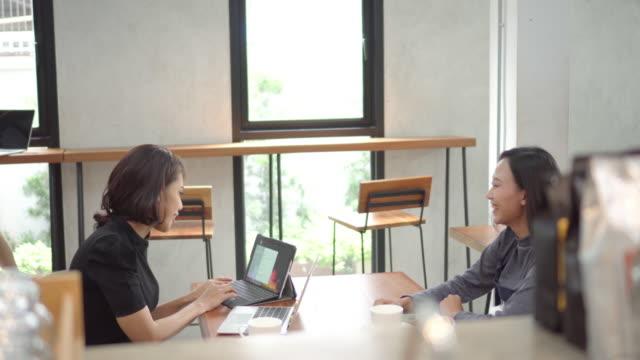 アジアの女性フリーランサー2人がノートパソコンを使ってコーヒーショップで働いている - ライフスタイル点の映像素材/bロール