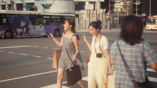 vídeos y material grabado en eventos de stock de dos mujeres influencers asiáticas comprando y cruzando la calle (movimiento lento) - escapada urbana