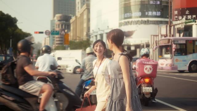 2人のアジアの女性インフルエンサーが買い物をして横断する(スローモーション) - taipei点の映像素材/bロール