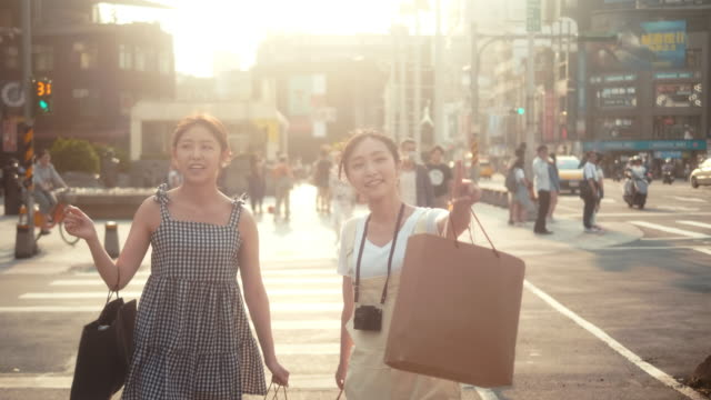 two asian female influencers with shopping bags crossing street - tracking shot stock videos & royalty-free footage
