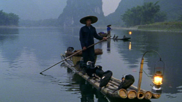 "two asian fishermen on ""sampan"" rafts on li river with cormorant fishing birds + lanterns / china - sampan stock videos & royalty-free footage"