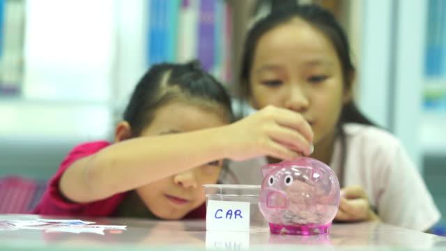 vídeos y material grabado en eventos de stock de dos chicas asiáticas aprenden a ahorrar depósito - ahorro