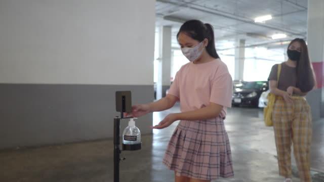 zwei asiatische mädchen und teenager eine mit hand desinfektionsmittel, alkohol-gel vor dem einsteigen in den supermarkt während covid-19 corona-virus - 16 17 jahre stock-videos und b-roll-filmmaterial