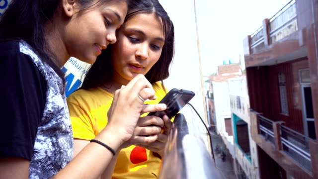 two asian girls busy on smart phone - india stock videos & royalty-free footage