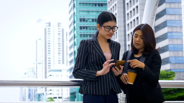Zwei asiatische glücklich Frau Geschäftskollegen über ein Projekt außerhalb in modernen Stadt zu diskutieren