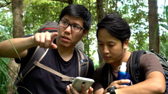 vídeos de stock e filmes b-roll de two asian looking on the navigator map in smartphone while trekking - encontrar