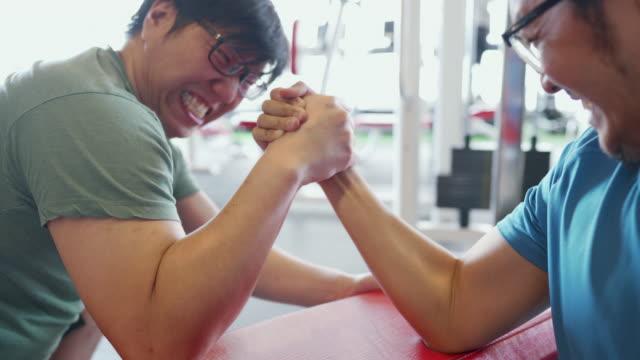 zwei asiatische mann im armwrestling konkurrieren, bevor einer von ihnen betrügt, indem sie einem anderen die hand beißen - armdrücken stock-videos und b-roll-filmmaterial