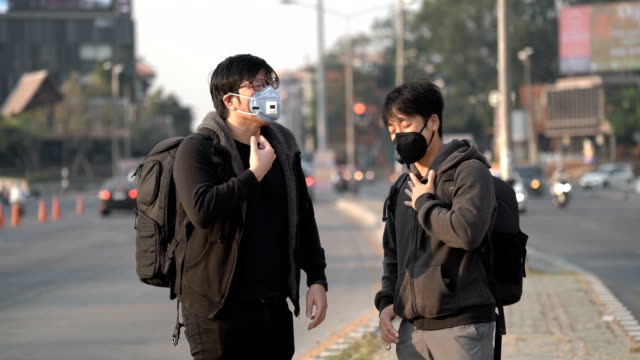 slo mo - two asian man discuss about direction and pollution with pollution mask on - asian man coughing stock videos & royalty-free footage