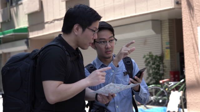 two asian man looking on map and using smartphone. - guide stock videos & royalty-free footage