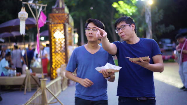 vídeos de stock e filmes b-roll de two asian men eating and exchanging their food for thai traditional market - povo tailandês