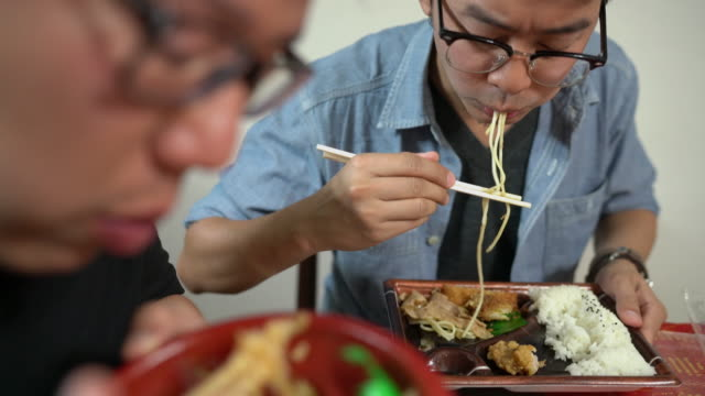 two asian men  eating bento, single-portion take-out or home-packed meal common in japanese cuisine. - happy meal stock videos and b-roll footage