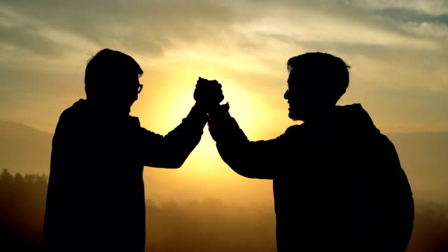 slo mo two asian men giving sport handshake on top of hill - partnership stock videos & royalty-free footage